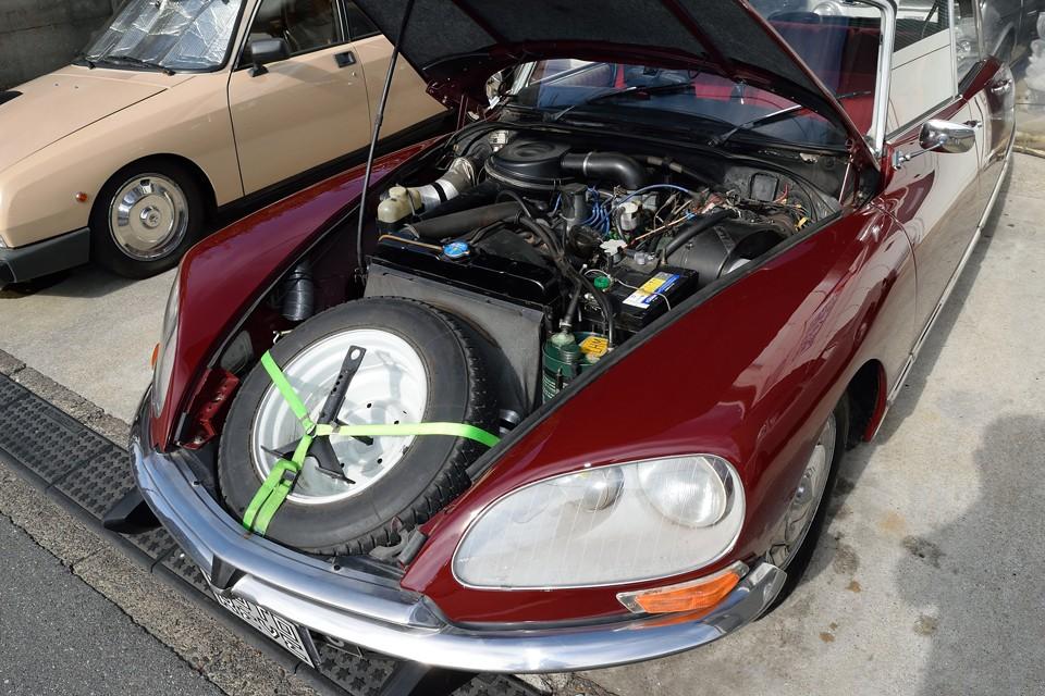 巨大なボンネットを開くと、ハイドロの油圧系統が張り巡らされ、他車とは少し様相が異なるエンジンルーム。DSをご覧になった方なら、これかなり手入れの行き届いた状態なのがお分かりいただけるかと・・・ちなみにスペアタイヤはこんなところにあるんです。なんで熱々になるボンネット内に置くのかは置いておいて(笑)