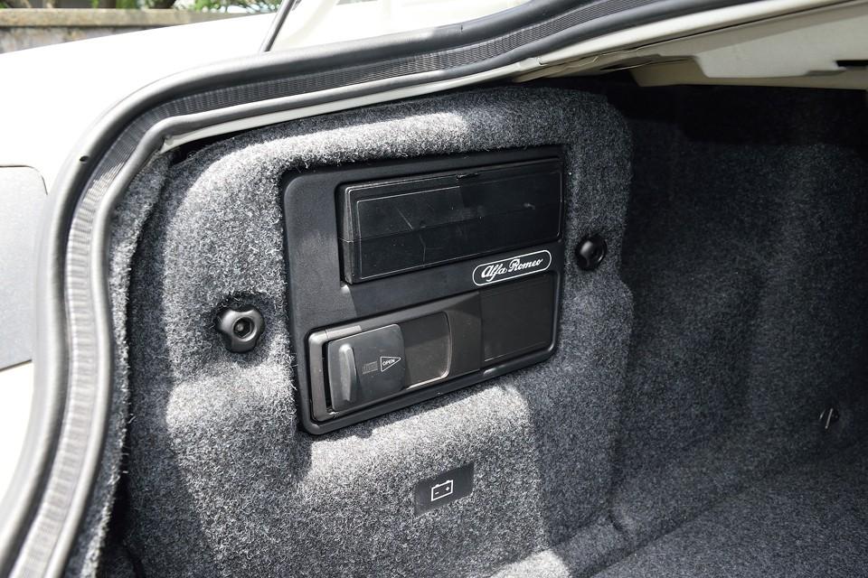 向かって左側にナビ本体、CDチェンジャー、バッテリーを収納!・・・ん?バッテリーがトランクにあって、トランクハッチが電動ロック式ということは、バッテリー上がったらどうすんの???ご安心ください、そんな時の為に、手動で開くボンネット内にバッテリー接続端子があります。